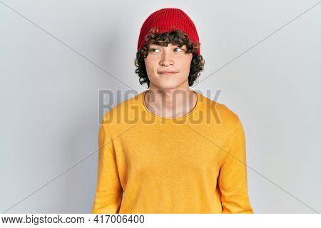 Handsome young man wearing wool hat smiling looking to the side and staring away thinking.