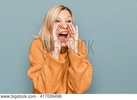 Middle age caucasian woman wearing casual winter sweater shouting angry out loud with hands over mouth