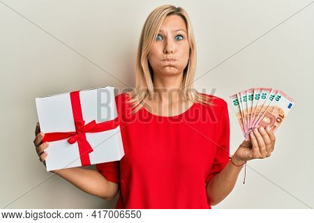 Middle age caucasian woman holding gift and euros banknotes puffing cheeks with funny face. mouth inflated with air, catching air.
