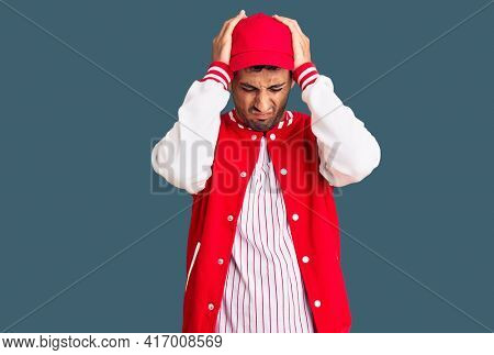 Young hispanic man wearing baseball uniform suffering from headache desperate and stressed because pain and migraine. hands on head.