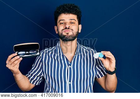 Young arab man with beard holding glasses and contact lenses puffing cheeks with funny face. mouth inflated with air, catching air.