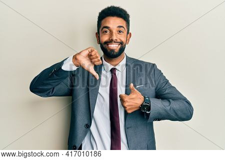 Handsome hispanic man with beard wearing business suit and tie doing thumbs up and down, disagreement and agreement expression. crazy conflict