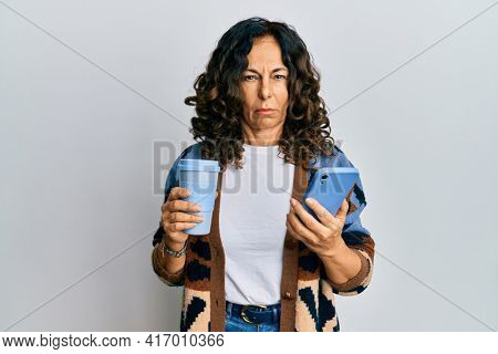 Middle age hispanic woman drinking a cup of coffee and looking at the smartphone screen skeptic and nervous, frowning upset because of problem. negative person.