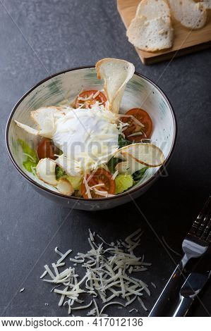 Poached Egg With Ceasar Salad Served In A Bowl