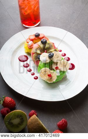 Three Donuts Served With Fruits And Berries