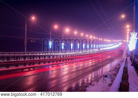Traces Of Headlights From Cars Moving At Winter Night On The Bridge. Lights Reflecting In The Wet As