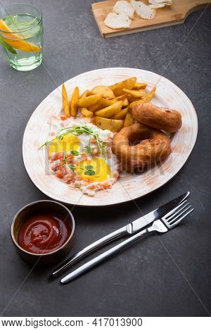 Donuts Served With Fried Eggs And Fried Potatoes For Breakfast
