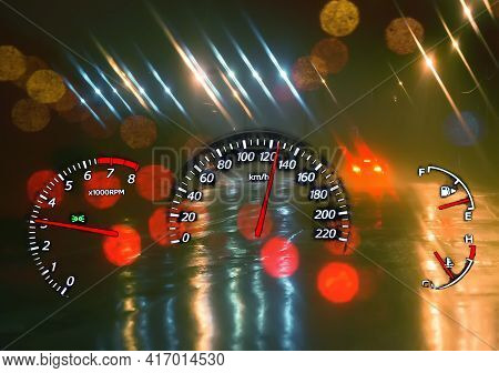 Speedometer And A Tachometer On A Background Of A Night Wet Road. Over Speed. Dangerous Driving.