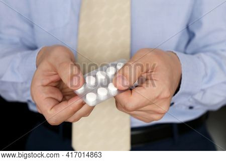 Man In Office Clothes Taking Pills, Pack Of Medication In Male Hands Close Up. Concept Of Antidepres