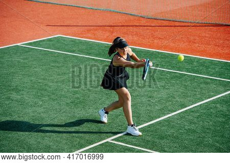 Sixting Year Old Girl Playing Tennis On A New Court, Returning Ball