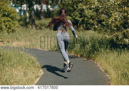 Running Girl In City Park. Young Woman Runner Outdoor Jogging. Back View.