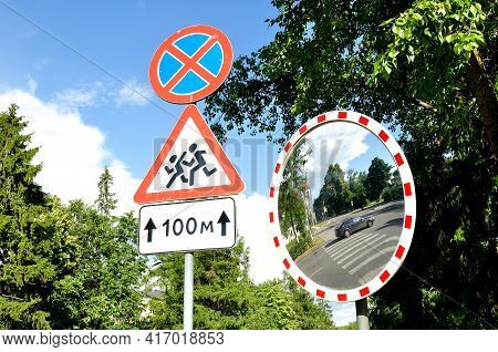 Spherical mirror. Mirror of spherical type reflecting the cross for improving visibility and road signs Stopping is prohibited and Caution Children.Spherical mirror at the intersection,spherical mirror at the road