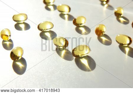 Shiny Yellow Fish Oil Capsules Isolated On A White Background With Shadows Of Focus On The Table. Vi