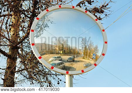 VELIKY NOVGOROD, RUSSIA - MARCH 26, 2016. Mirror of spherical type with dirty spots reflecting the cross for improving visibility and unidentified cars crossing the road,spherical mirror closeup,spherical mirror at the road