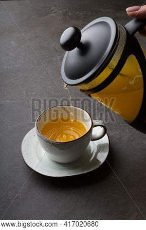 French Press With Yellow Herbal Tea On A Dark Table