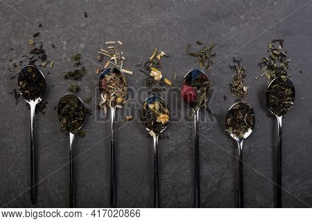 Different Sorts Of Dry Tea Leaves Set With Spoons On A Dark Background