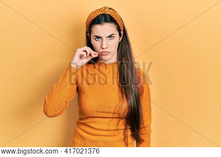 Young brunette teenager wearing casual yellow sweater mouth and lips shut as zip with fingers. secret and silent, taboo talking
