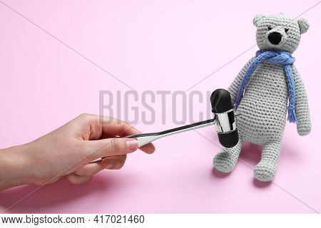 Woman Pretending To Test Teddy Bear's Reflexes With Hammer On Pink Background, Closeup. Nervous Syst