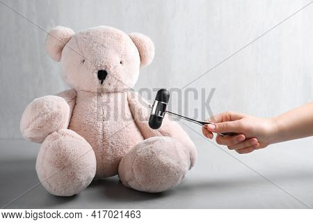 Woman Pretending To Test Teddy Bear's Reflexes With Hammer On Grey Background, Closeup. Nervous Syst