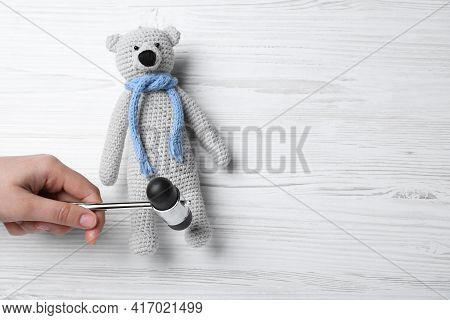 Woman Pretending To Test Teddy Bear's Reflexes With Hammer On White Wooden Background, Top View And