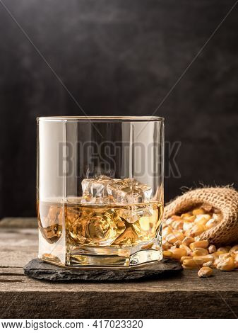 A Glass Of Classic Corn Whiskey (bourbon) On A Wooden Table. Vertical Photo.