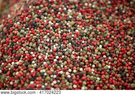 A mixture of green, black, white and red peppers. Spices are solding in outdoor market, Sicily, Italy