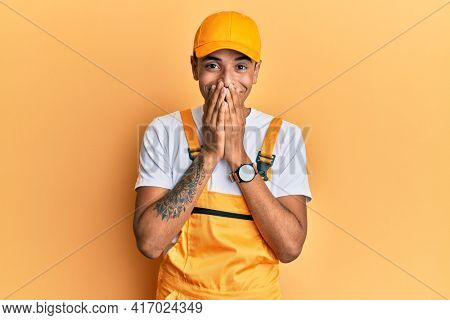Young handsome african american man wearing handyman uniform over yellow background laughing and embarrassed giggle covering mouth with hands, gossip and scandal concept