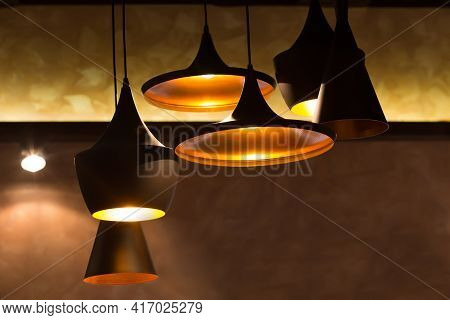 Metal Fixtures Of Various Shapes With Lights On The Ceiling In The Room