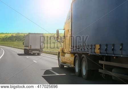 Big Trucks Drive On A Country Road In Summer