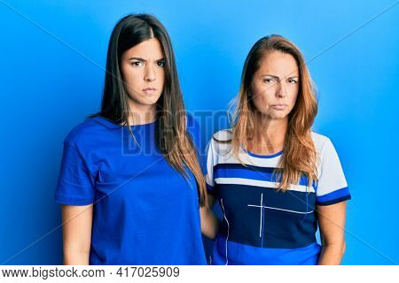 Hispanic family of mother and daughter wearing casual clothes over blue background skeptic and nervous, frowning upset because of problem. negative person.