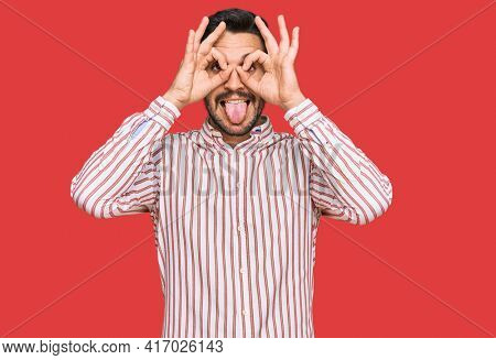 Young hispanic man wearing business shirt doing ok gesture like binoculars sticking tongue out, eyes looking through fingers. crazy expression.