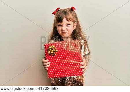 Little caucasian girl kid holding red gift skeptic and nervous, frowning upset because of problem. negative person.