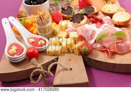antipasto platter with ham,  cheese,  canape, olives on wooden board