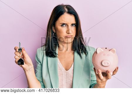 Middle age brunette woman holding house keys and piggy bank skeptic and nervous, frowning upset because of problem. negative person.