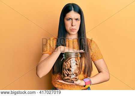 Young hispanic woman holding jar with chocolate chips cookies skeptic and nervous, frowning upset because of problem. negative person.