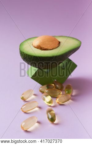 A Half Of  Green Avocado On The Catwalk With Omega 3 With Pink Background. Front View.