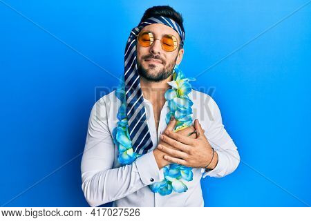 Young hispanic businessman wearing party funny style with tie on head smiling with hands on chest with closed eyes and grateful gesture on face. health concept.