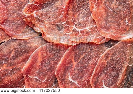 Sliced carpaccio. Raw beef meat. Top view.