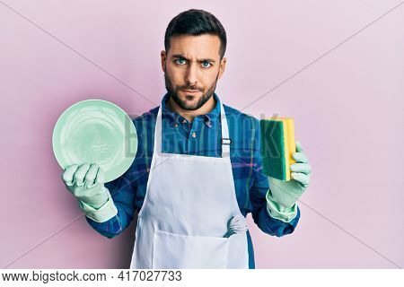 Young hispanic man wearing apron holding scourer washing dishes skeptic and nervous, frowning upset because of problem. negative person.