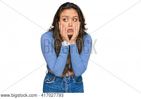 Young hispanic girl wearing casual clothes tired hands covering face, depression and sadness, upset and irritated for problem