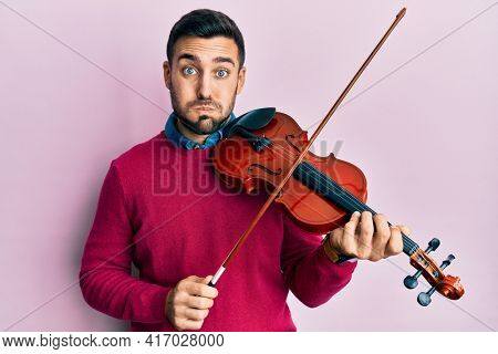 Young hispanic musician man playing violin puffing cheeks with funny face. mouth inflated with air, catching air.