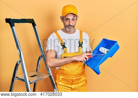 Handsome middle age man with grey hair holding roller painter skeptic and nervous, frowning upset because of problem. negative person.