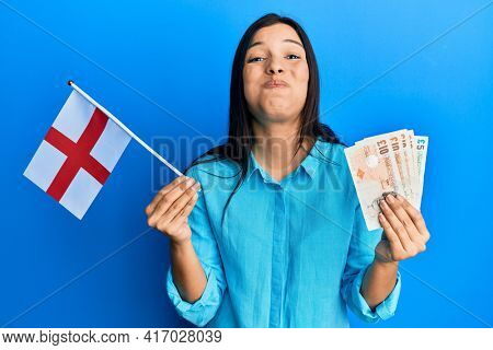 Young latin woman holding england flag and pounds banknotes puffing cheeks with funny face. mouth inflated with air, catching air.
