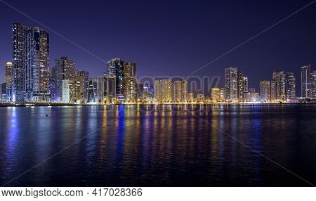 Sharjah,uae - Dec 2nd 2020. Panoramic View Of The Illuminated Sky Scrappers Showing Beautiful Reflec