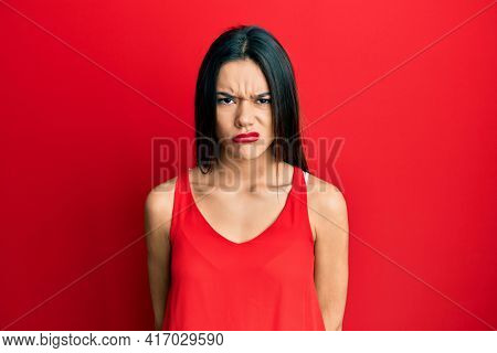 Young hispanic girl wearing casual style with sleeveless shirt skeptic and nervous, frowning upset because of problem. negative person.