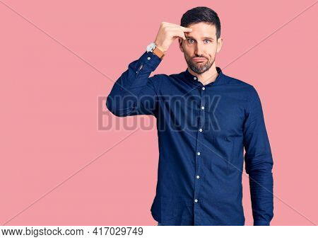 Young handsome man wearing casual shirt worried and stressed about a problem with hand on forehead, nervous and anxious for crisis