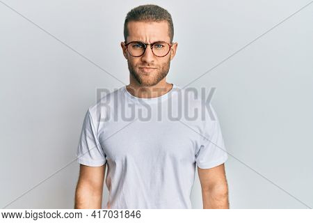 Young caucasian man wearing casual clothes and glasses skeptic and nervous, frowning upset because of problem. negative person.