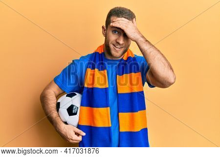 Young caucasian man football hooligan cheering game holding ball stressed and frustrated with hand on head, surprised and angry face