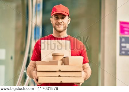 Young caucasian deliveryman smiling happy holding delivery food at the city.