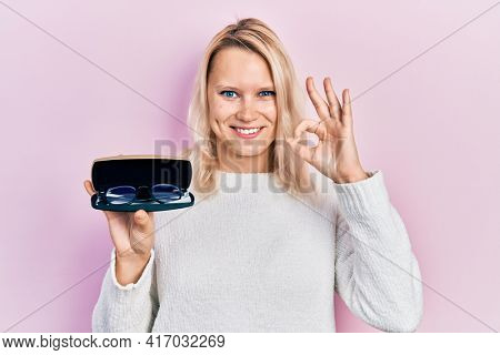 Beautiful caucasian blonde woman holding glasses in eyewear case doing ok sign with fingers, smiling friendly gesturing excellent symbol